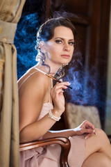 Pretty woman is sitting on the chair and smoking cigarette. Blue