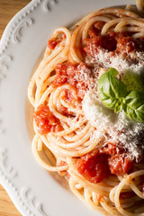 dish with spaghetti and tomato sauce on the wooden table