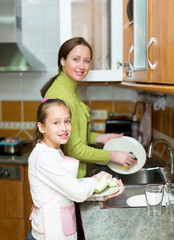 girl  with mother washing dishes