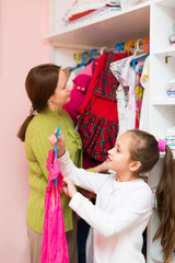mam teaching girl to choose clothes