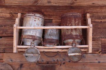 Alte Holzwand mit Milchkannen