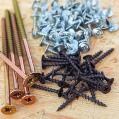 Screws of different sizes on wooden background