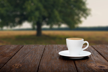 Coffee on wooden table with beautiful field background