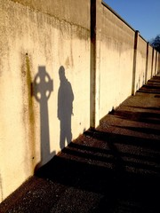 man praying ar celtic cross shadow