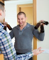 Guys with beer bottles at doorway