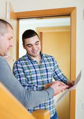Two men at apartment doorstep