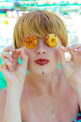 Playful girl holding donuts on her eyes.