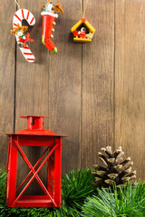 christmas decoration with red candlestick and brown pine cone on