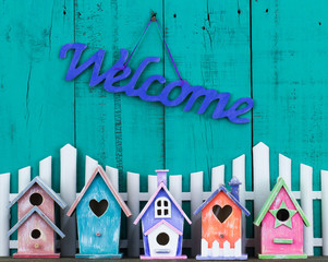 Welcome sign by white picket fence and colorful birdhouses