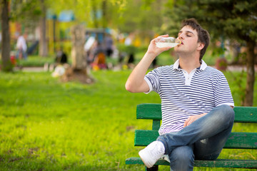 Young man drinking mineral water in green park