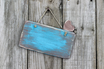 Blank sign with heart hanging on wooden background