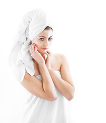 Woman in headband with lifting cream applied on a half of her fa