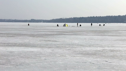 many fishermen are fishing on a lake in early spring
