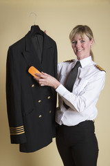 Female airline captain brushing her uniform jacket