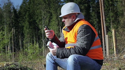 Lumberjack with money and cell phone in forest