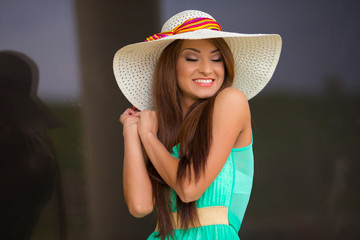 Beautiful young woman in elegant hat and sunglasses posing with