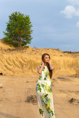 stunning, cute woman with long hair in dress near sandy mountain