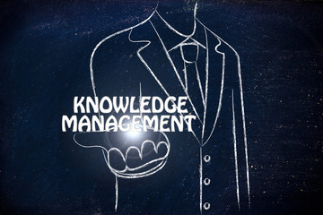 business man handing out the word Knowledge Management