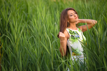 cute brunette woma with long hair posing in high grass field.