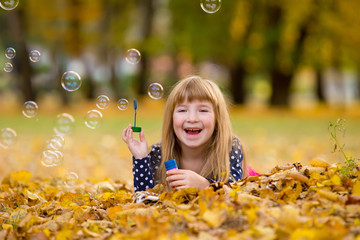 caucasian child girl blowing soap bubbles outdoor at autumn suns