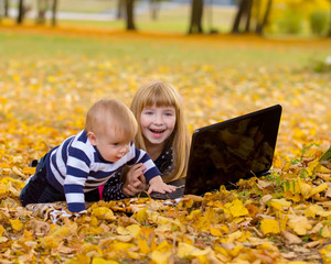 Little smiling girl and brother boy using laptop in a autumn gar
