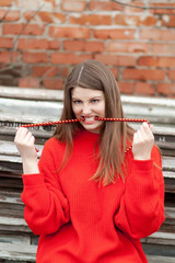 Young girl in old, red sweater with chaplet in mouth with teeth.