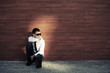Young business man in depression sitting at the wall