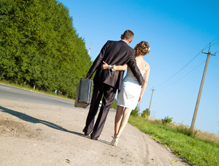 young just married pair walking along the road