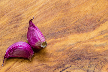 Organic garlic cloves on wooden table background
