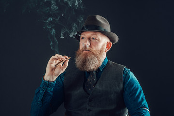 Man with Goatee in Trendy Wear Smoking a Cigarette