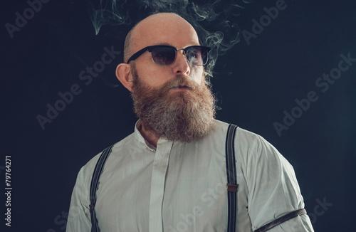 Stylish Bald Goatee Male Smoker on Gray Background - 79764271