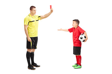 Football referee showing red card to a boy