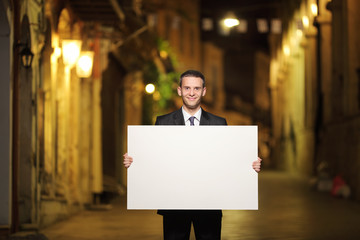 Businessman holding a panel in a city street