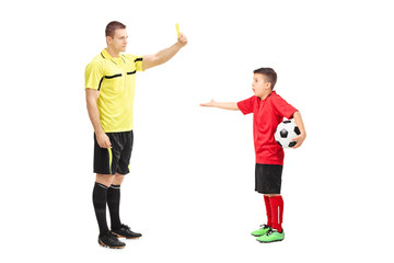 Football referee showing yellow card to a boy
