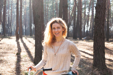 Beautiful young woman on bike in sunny park
