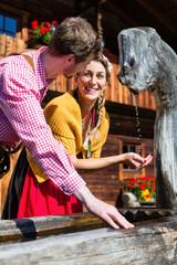 Paar vor Berghütte an Brunnen trinkt Wasser
