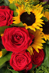 Red roses and sunflowers in a floral arrangement