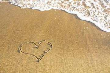 Heart drawn on the sand of a sea beach.