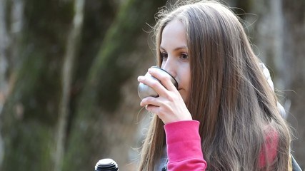 Girl pours tea from a thermos and drink
