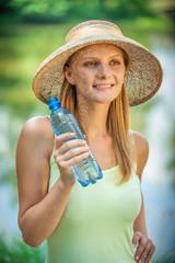 Girl in straw hat drinks water