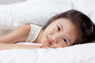 Lovely Asian child laying down on the bed