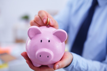 Businessman putting  money into a piggy bank isolated on white