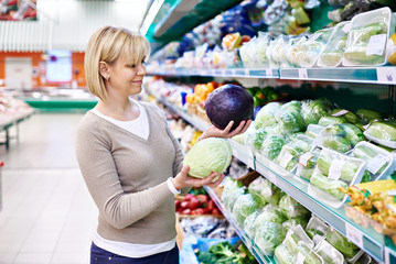 Woman buys a red and white cabbage in store