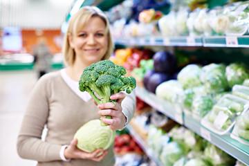 Happy woman showing broccoli