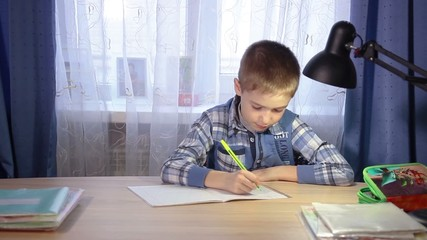child doing homework, writing in a notebook in the evening at