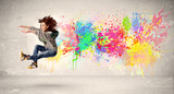 Fototapety Happy teenager jumping with colorful ink splatter on urban backg