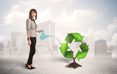 Business woman watering green recycle sign tree on city backgrou