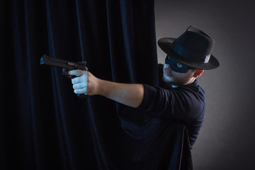 The robber or bandit in a mask shoots a gun.