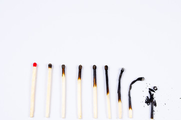 matches in different stages of burning on white