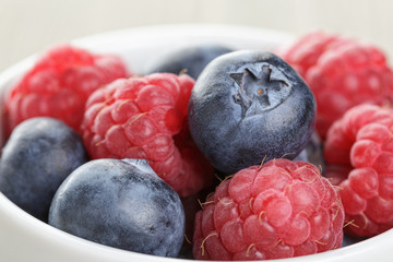 blueberries and raspberries in bowl on wooden table
